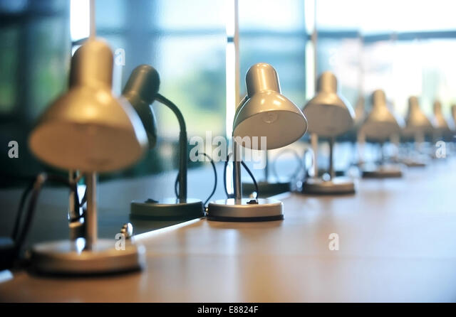 Several reading library lamps in a row on a desk - Stock Image