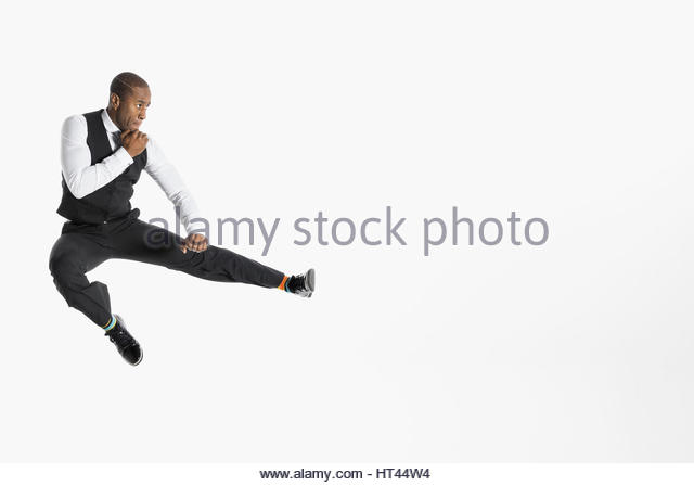 Businessman jumping and kicking in fighting stance against white background - Stock-Bilder