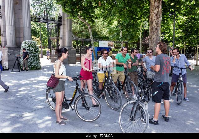 Spain Europe Spanish Madrid Retiro Parque del Buen Retiro city park bicycle bicycles Hispanic man woman guide speaking - Stock Image