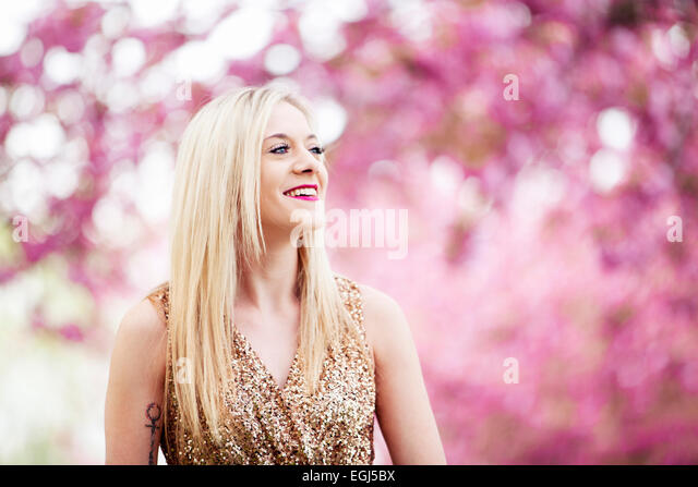 Young woman looking happy in the distance, outside, portrait, - Stock Image