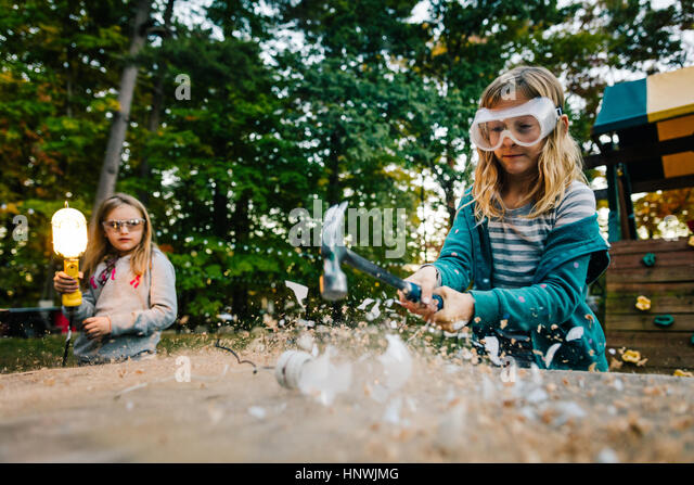 Girl smashing lightbulb with hammer on garden table at dusk - Stock Image