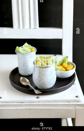 Kiwi ,mango and chia seeds pudding in jar for breakfast - Stock Image