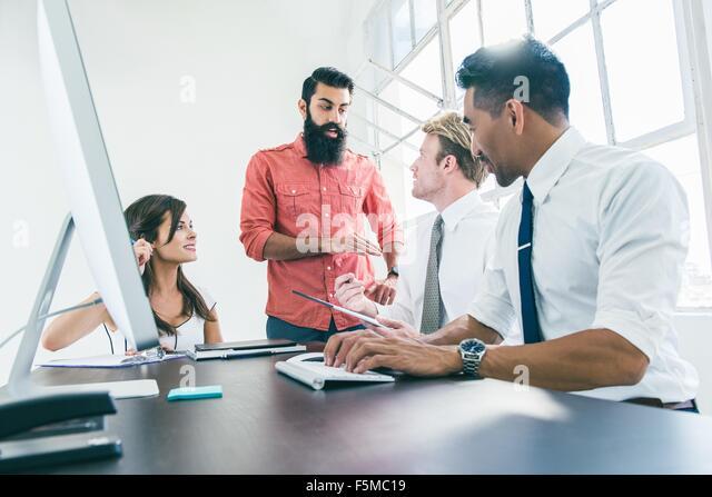 Business people in brainstorming meeting by office window - Stock Image
