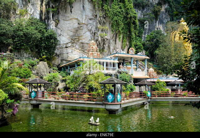 Exterior of a hindu temple in nature, between a pond and a cliff face, with cave behind. Hinduism, religion, religious - Stock Image