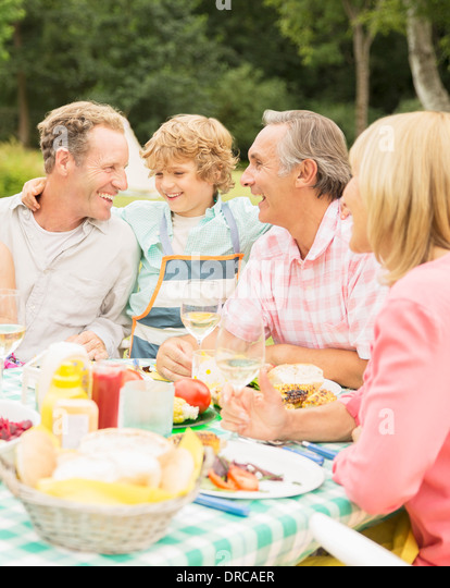 Family enjoying lunch at table in backyard - Stock Image