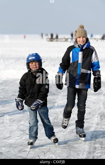 Boys ice skating, playing ice hockey, St. Heinrich, Lake Starnberg, Five Lakes region, Upper Bavaria, Bavaria - Stock Image