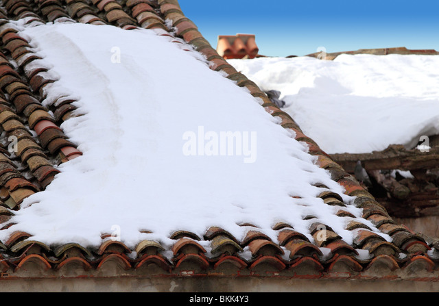 aged clay roof tiles snowed under snow architecture detail - Stock Image