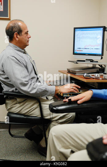 Police polygraph operator administering a lie detector test to a male subject. United States. - Stock Image