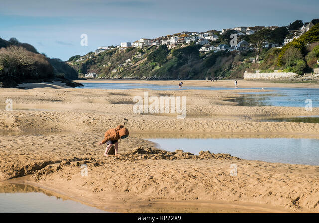 A young boy digging in the sand at low tide on the Gannel Estuary. Newquay, Cornwall, UK. - Stock Image