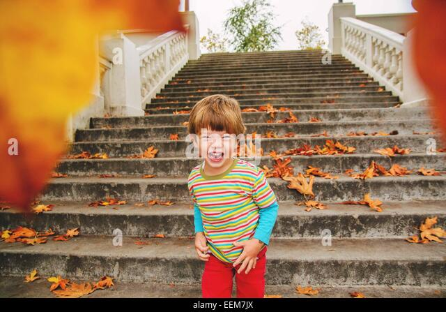 Boy (2-3) laughing after throwing leaves at camera - Stock Image