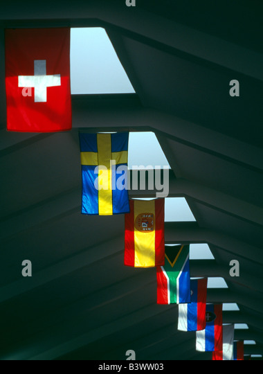 International flags hang from the ceiling of an airport - Stock Image
