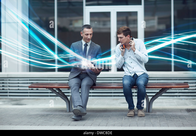 Businessman and young man watching digital tablet and waves of illumination - Stock Image