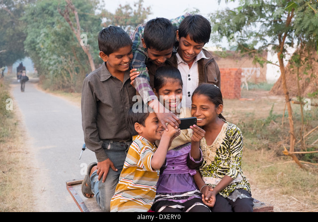 India, Uttar Pradesh, Agra, six children riding on the back of a bicycle trailer looking at a smart phone - Stock-Bilder
