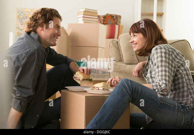 Couple having lunch break whilst moving - Stock Image
