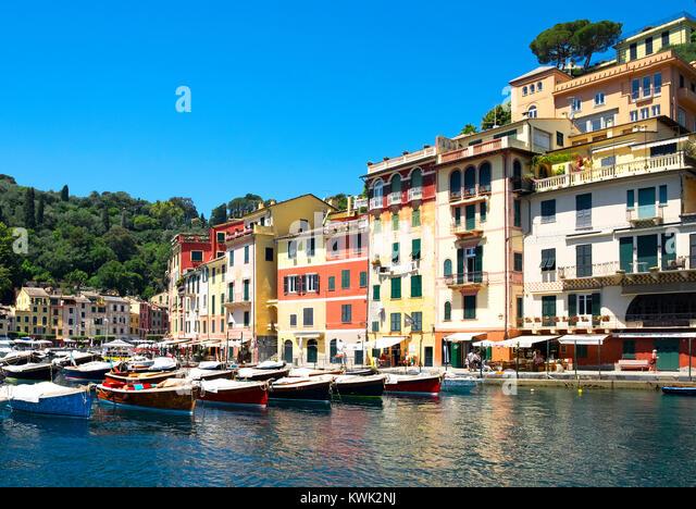 colorful homes and fishing boats around the harbor in portofino, genoa, italy. - Stock Image