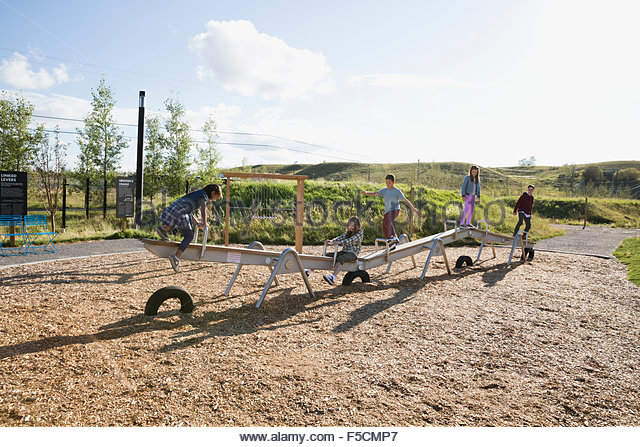 Kids playing on long seesaw at sunny playground - Stock Image
