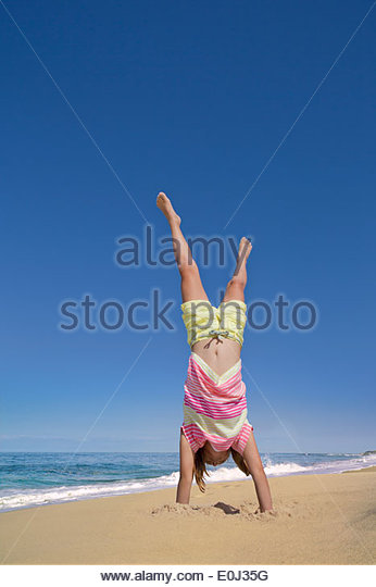 Girl doing handstand on sunny beach - Stock Image