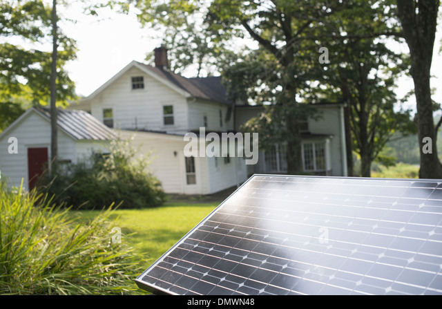 A solar panel in a farmhouse garden. - Stock Image