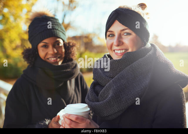 Two girlfriends looking at camera and smiling while holding coffee to go - Stock Image