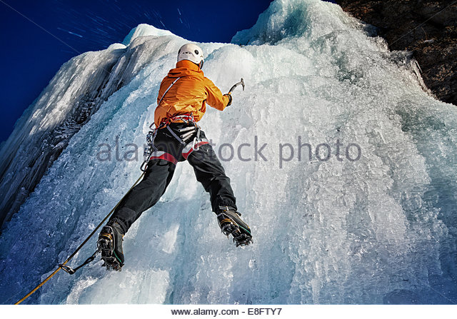 USA, Colorado, Hinsdale County, Lake City, Ice climber hanging from ice with ice tools - Stock Image