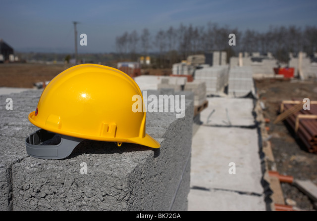 hard hat sitting on a pile of breeze concrete building blocks on stopped construction building site in northern - Stock Image