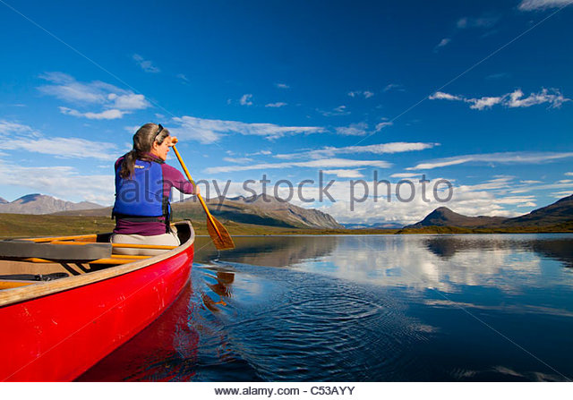 Woman tandem canoeing on Tangle Lakes off the Denali Highway, Alaska Range, Interior Alaska, Autumn - Stock Image