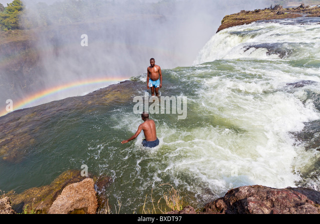 Man jumps into Devil's Pool at Victoria Falls. - Stock-Bilder