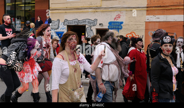 Panorama of a mob of Zombies with fake blood and make up trudging along in the annual Toronto Zombie walk - Stock Image