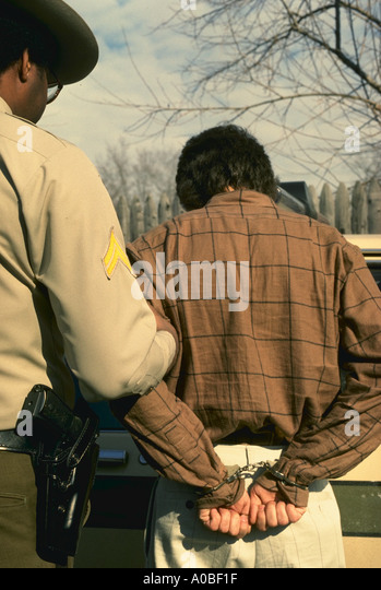 Policeman and man in handcuffs model released - Stock Image