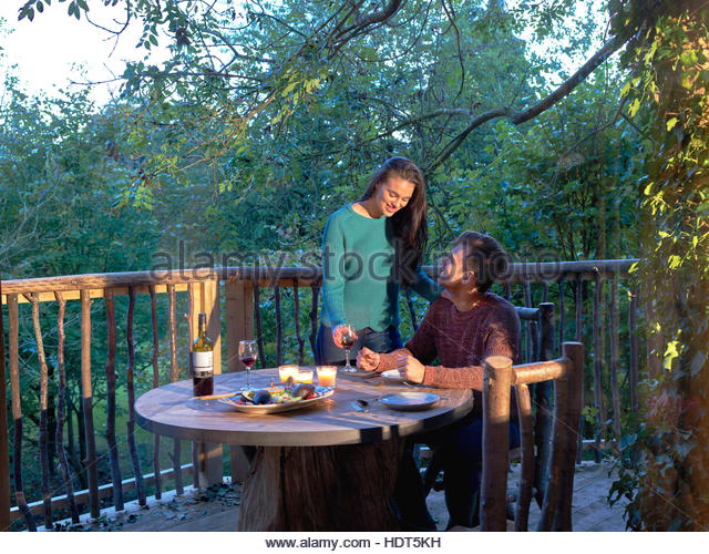Young couple drinking wine together on log cabin balcony. - Stock Image