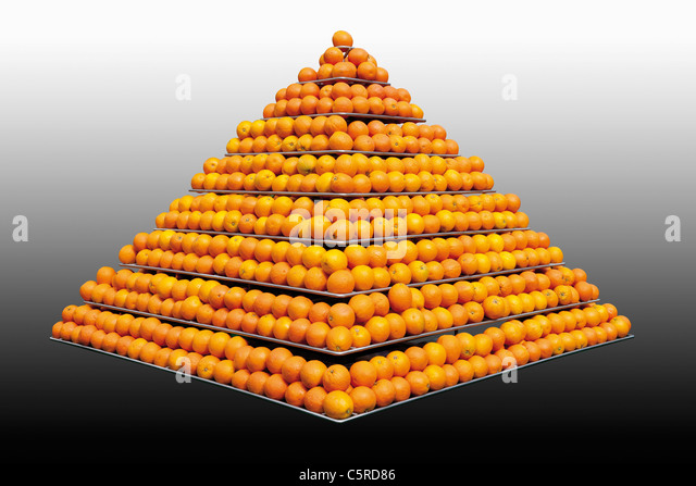 Stack of oranges in pyramid shape against grey background - Stock Image