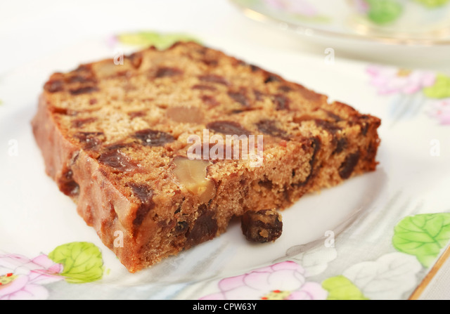A fruit cake with walnuts which contains no fat, known as Irish Tea Bread. On pretty floral crockery for afternoon - Stock Image