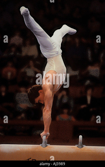 Russian male gymnast in a balanced position whilst competing on the Pommel Horse apparatus - Stock Image