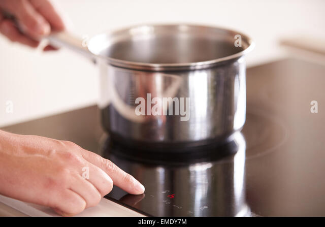 Close Up Of Man Selecting Temperature On Cooker Hob - Stock Image