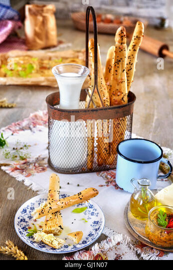 Bread sticks with milk, breakfast rustic setting on a wooden table. - Stock Image