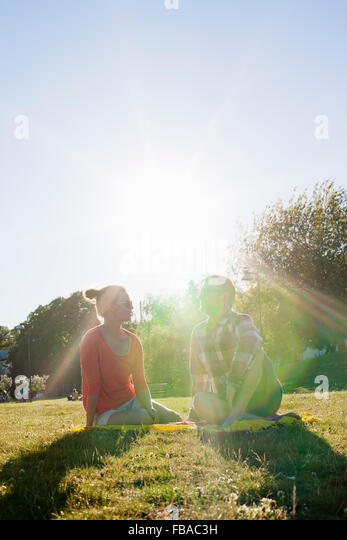 Finland, Uusimaa, Helsinki, Kaivopuisto, Young woman and man sitting in park on sunny day - Stock Image