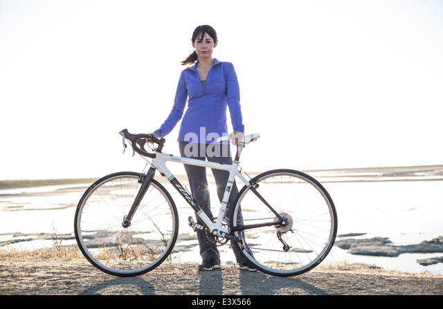 Sporty woman with bicycle stands in a newly developed recreational trail. - Stock Image