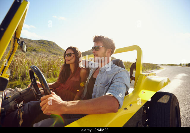 Beautiful young couple sitting in their car and enjoying the road trip. Man driving a car on an open road. Couple - Stock Image