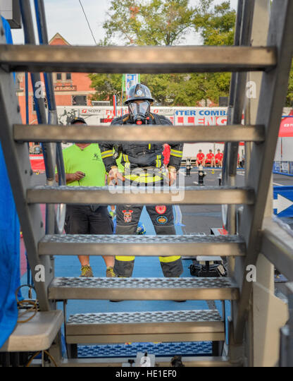 A firefighter waiting to climb a four story tower during competition. - Stock Image