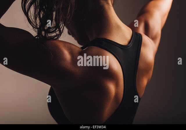 Close-up shot of back of female fitness model. Young woman in sports wear with muscular body. - Stock Image