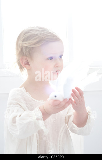 Little girl holding fake dove - Stock Image