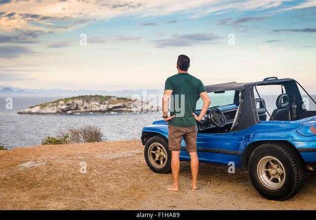Rear view of male tourist looking out to Branca island, Buzios, Rio de Janeiro, Brazil - Stock-Bilder
