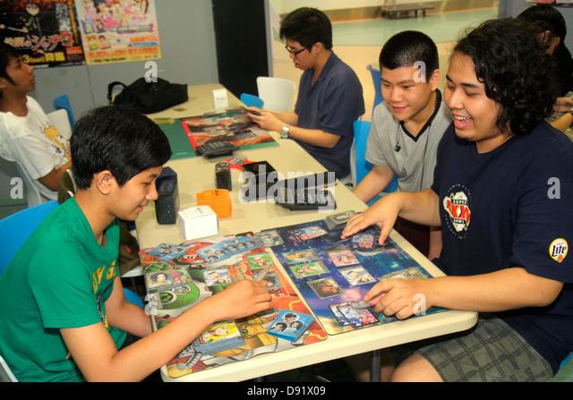 Bangkok Thailand Chatuchak Phaholyothin Road Asian man teen boy trading cards fantasy role playing card game - Stock Image