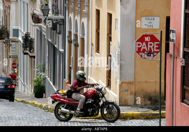 Puerto Rico Old San Juan Calle del Sol architecture steep hill motorcycle adoquine cobblestone stop sign - Stock Image