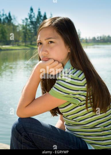 Teen Vietnamese/Caucasian girl sits outside.MR  © Myrleen Pearson - Stock-Bilder