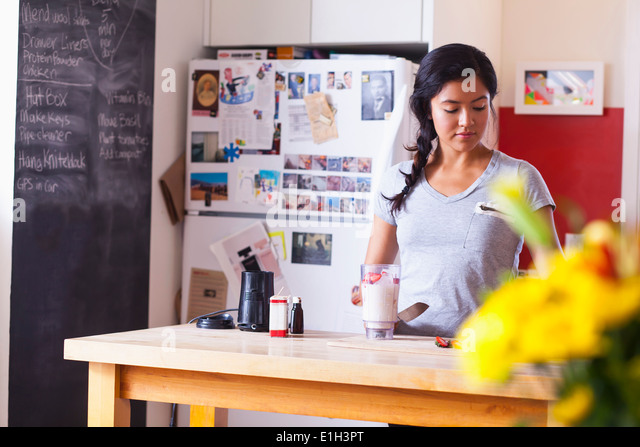 Young woman blending fruits in kitchen - Stock Image
