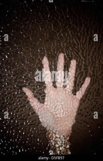 Imprisoned woman's hand pressing against glass - Stock Image