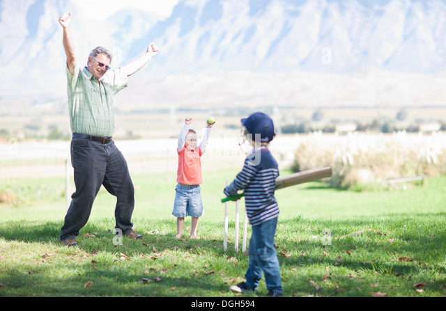 Boys grandfather playing cricket - Stock Image