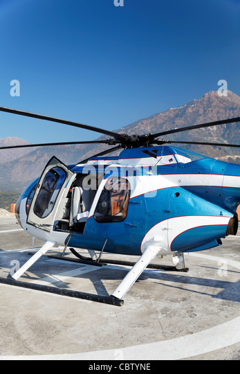 Abstract portrait of small metallic blue and white helicopter stationed on a helipad with open door, blue skies - Stock Image