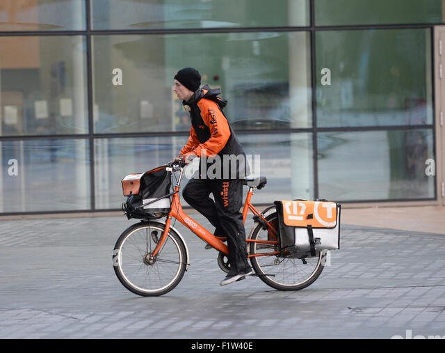 A TNT postman delivers mail to an address in Media City Manchester. - Stock Image